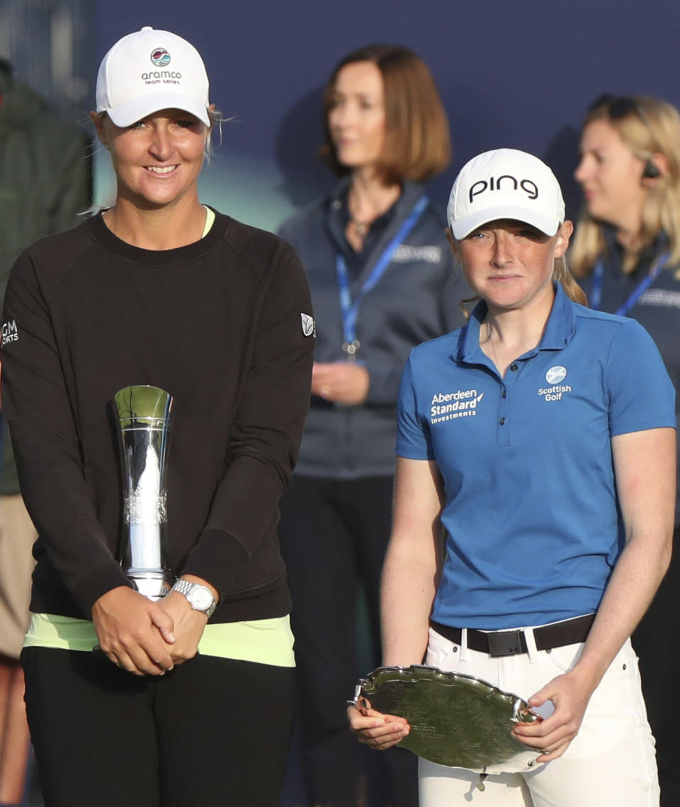 Sweden's Anna Nordqvist poses for the media holding the trophy after winning the Women's British Open golf championship, with Louise Duncan holding the leading amateur Scotland's Louise Duncan during the presentation ceremony in Carnoustie, Scotland, Sunday, Aug. 22, 2021. (AP Photo/Scott Heppell)