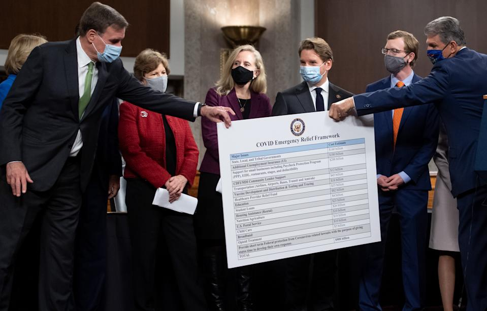 US Senator Joe Manchin (R), Democrat of West Virginia, hands a poster describing a proposal for a Covid relief bill to US Senator Mark Warner (L), Democrat of Virginia, alongside a bipartisan group of Democrat and Republican members of Congress as they announce the proposal on Capitol Hill in Washington, DC, on December 1, 2020. (Photo by SAUL LOEB / AFP) (Photo by SAUL LOEB/AFP via Getty Images)