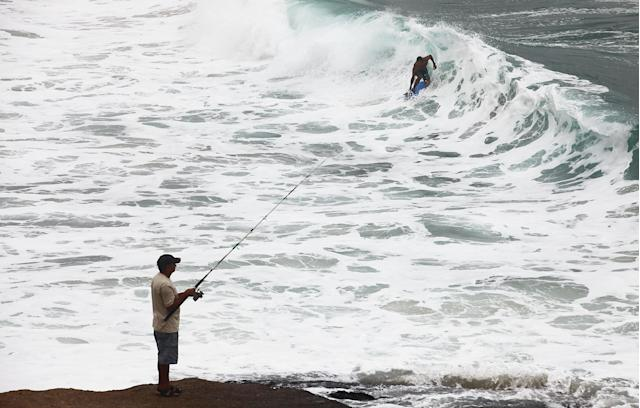 RIO DE JANEIRO, BRAZIL - APRIL 16: A man fishes as another surfs at Arpoador on April 16, 2014 in Rio de Janeiro, Brazil. A cold front delivered rains and heavy surf to Rio the past two days. The 2014 FIFA World Cup begins in Brazil June 12. (Photo by Mario Tama/Getty Images)