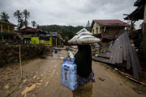 A villager carrying donated rice and other necessities as she looks at the damaged caused by the flood in Kampung Manek Urai Lama. – The Malaysian Insider pic by Hasnoor Hussain, December 30, 2014.