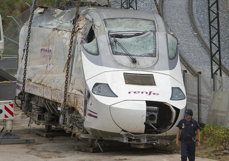 Police stand guard as a wreckage of a crashed train is seen ready to be deposited in Santiago de Compostela, Spain, Sunday July 28, 2013. Spain's interior minister Jorge Fernandez Diaz says the driver whose speeding train crashed, killing 78 people, is now being held on suspicion of negligent homicide. The Spanish train derailed at high speed Wednesday killing 78 and injuring dozens more. (AP Photo/Lalo R. Villar)