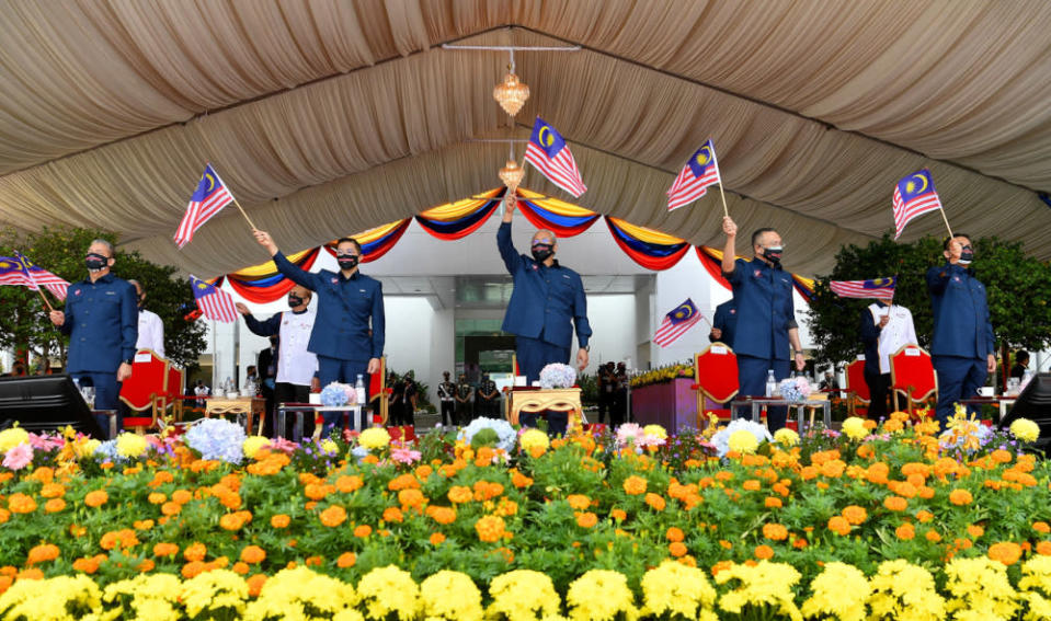 Malaysian Cabinet ministers wave the Jalur Gemilang during National Day celebrations in Putrajaya  August 31, 2021. — Bernama pic