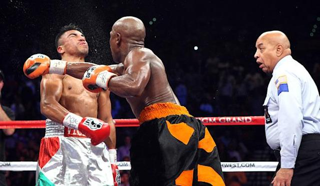 AFP PICTURES OF THE YEAR 2011 Floyd Mayweather Jr. slams a right to the head of WBC Welterweight Champion Victor Ortiz in the 4th round as referee Joe Cortez looks on, ending the fight on September 17, 2011 at the MGM Grand Garden Arena in Las Vegas. Mayweather beat Ortiz in a knockout to win the WBC Welterweight title. (Photo by John Gurzinski/AFP/Getty Images)