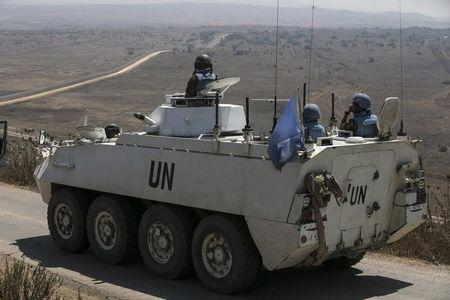 Members of the UNDOF ride an APC in the Israeli-occupied Golan Heights before crossing into Syria