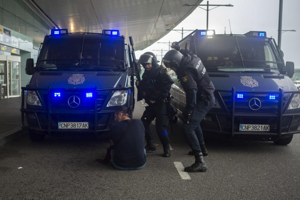 In this Monday, Oct. 14, 2019 photo, Spanish police clash with a pro-independence protester during a demonstration at El Prat airport, outskirts of Barcelona, Spain. Riot police engaged in a running battle with angry protesters outside Barcelona's airport Monday after Spain's Supreme Court convicted 12 separatist leaders of illegally promoting the wealthy Catalonia region's independence and sentenced nine of them to prison. (AP Photo/Joan Mateu)