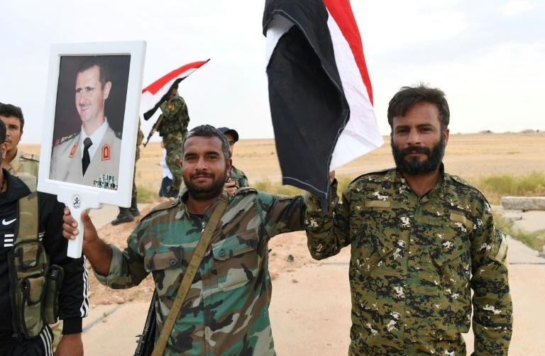 Syrian government forces raise a national flag and a picture of President Bashar al-Assad  at Tabqa air base in northern Syria's Raqa region on October 16, 2019