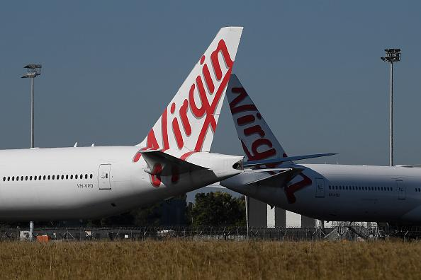 Virgin Australia aircrafts are seen parked in the Brisbane Airport. Passengers on board flight VA962 have been warned to monitor for coronavirus symptoms after a woman tested positive..