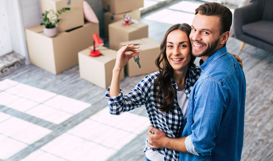 A young couple holds happily a key to their new home which they were so excited about, and this can't but make them feel overwhelmed with positive emotions.