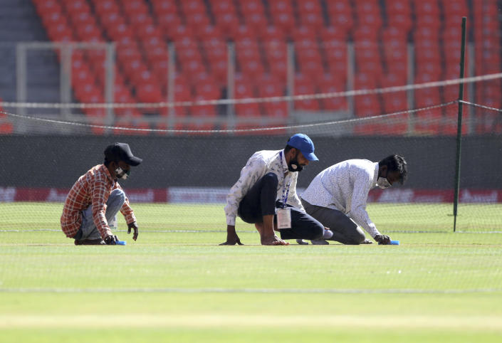 Ground staff work in the pitch area ahead of the fourth test cricket match between India and England at Narendra Modi Stadium in Ahmedabad, India, Wednesday, March 3, 2021. (AP Photo/Aijaz Rahi)