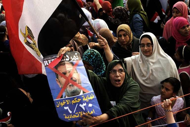 Opposition protesters shout slogans and show a defaced poster of their president on July 2, 2013 in Cairo