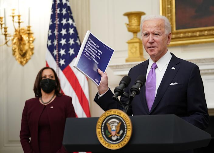 US President Joe Biden speaks about the Covid-19 response as US Vice President Kamala Harris (L) looks on before signing executive orders in the State Dining Room of the White House in Washington, DC, on January 21, 2021. (Photo by MANDEL NGAN / AFP) (Photo by MANDEL NGAN/AFP via Getty Images)
