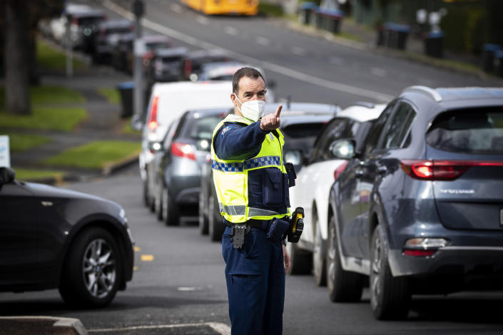 Police control the long vehicle line waiting for COVID-19 testing in Auckland, New Zealand, Thursday, Aug. 19, 2021. Japan, Australia and New Zealand all got through the first year of the coronavirus pandemic in relatively good shape, but now are taking diverging paths in dealing with new outbreaks of the fast-spreading delta variant. (Jason Oxenham/New Zealand Herald via AP)