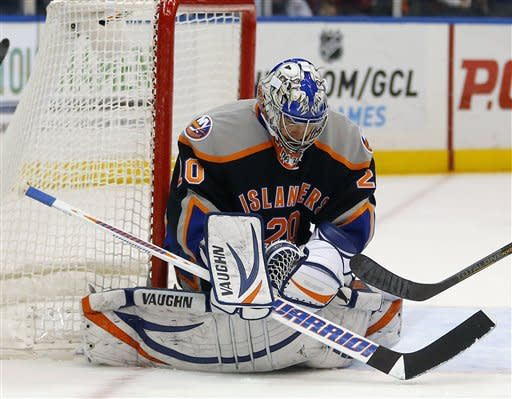 New York Islanders goalie Evgeni Nabokov (20) makes a save in the first period of an NHL hockey game against the Washington Capitals at the Nassau Coliseum in Uniondale, N.Y., Saturday, March 9, 2013. (AP Photo/Paul J. Bereswill)