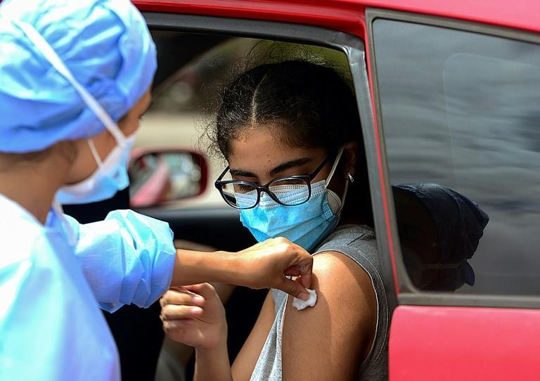 A teenager receives the first dose of the Pfizer/BioNTech Covid-19 vaccine in Tegucigalpa, on September 25, 2021 (AFP/ORLANDO SIERRA)