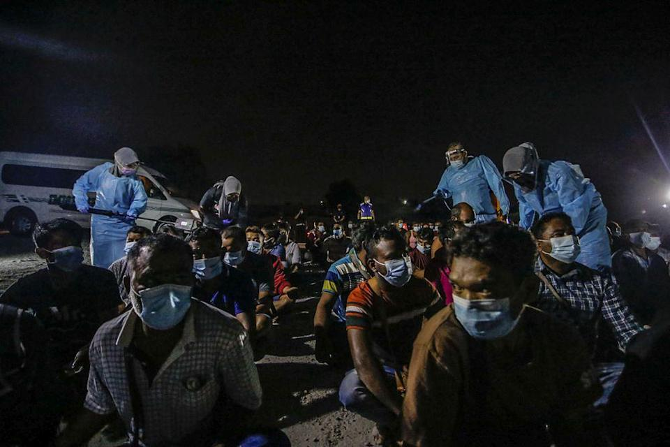 Immigration Department spray disinfectant on foreign workers during a raid on a construction site in Cyberjaya June 6, 2021. — Picture by Hari Anggara
