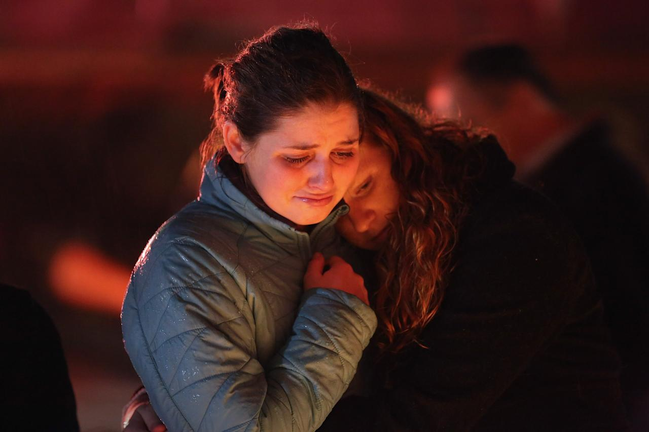 NEWTOWN, CT - DECEMBER 18:  Rachel Berger (L), and Greta Waag embrace while visiting a makeshift memorial for shooting victims on December 18, 2012 in Newtown, Connecticut. Funeral services were held in Newtown Tuesday for Jessica Rekos and James Mattioli, both age six, four days after 20 children and six adults were killed at Sandy Hook Elementary School.  (Photo by John Moore/Getty Images)