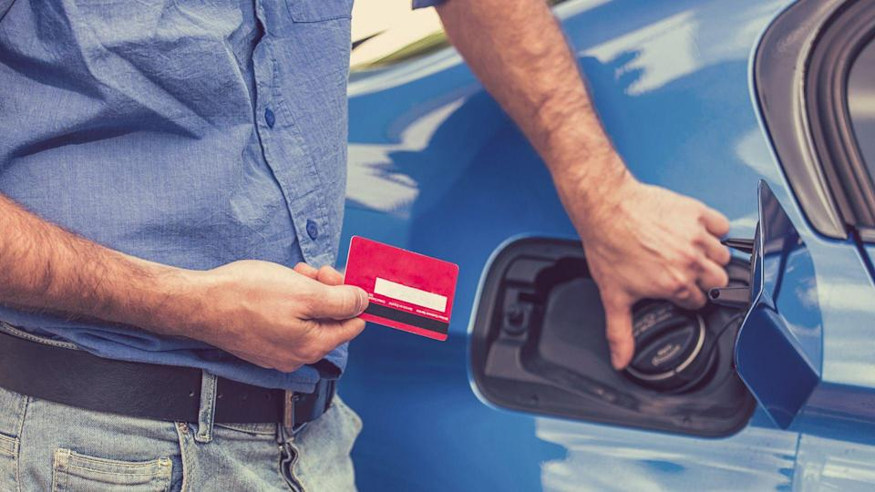 Man with credit card opening fuel tank of his new car.