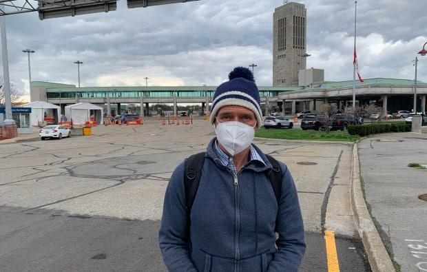 Greg Peacock of Toronto walked across the Rainbow Bridge in Niagara Falls, Ont., into Canada on the morning of April 15 after flying from Los Angeles to Buffalo, N.Y. He's been using the land crossing instead of flying directly to Toronto to avoid the quarantine hotel stay that is mandatory for air travellers. (Laura Clementson/CBC - image credit)