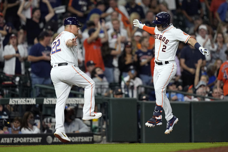 Houston Astros' Alex Bregman (2) celebrates with third base coach Omar Lopez after hitting a home run against the Tampa Bay Rays during the sixth inning of a baseball game Tuesday, Sept. 28, 2021, in Houston. (AP Photo/David J. Phillip)