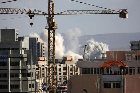 A construction crane is seen as smoke rises from Yarmouk Palestinian camp in Damascus