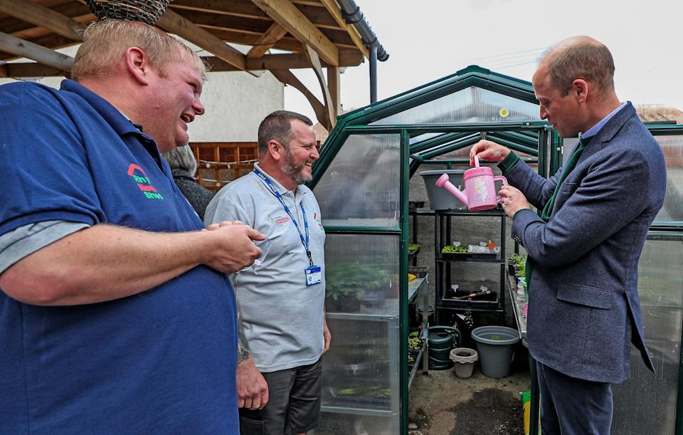 Britain's Prince William, Duke of Cambridge (R) holds a pink watering can during his visit to Brighter Futures, a consortium of eight local groups which encourage loal people to participate in community activities, in Rhyl, Denbighshire, Wales on May 6, 2021. (Photo by Peter Byrne / POOL / AFP) (Photo by PETER BYRNE/POOL/AFP via Getty Images)