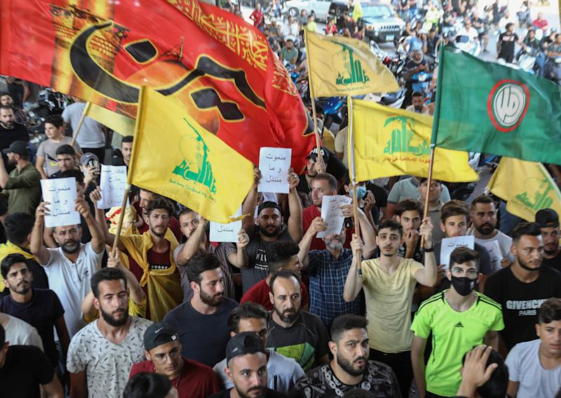 Image: Supporters of the Lebanese Shiite movements Hezbollah and Amal lift flags and placards as they protest a statement made by the US ambassador criticising the group, at a rally in the southern suburb of the capital Beiru (Anwar Amro / AFP - Getty Images)