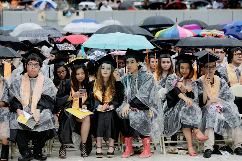New graduates hold umbrellas to keep dry during the Bergen Community College commencement at MetLife Stadium in East Rutherford, N.J., Thursday, May 17, 2018. (AP Photo/Seth Wenig)