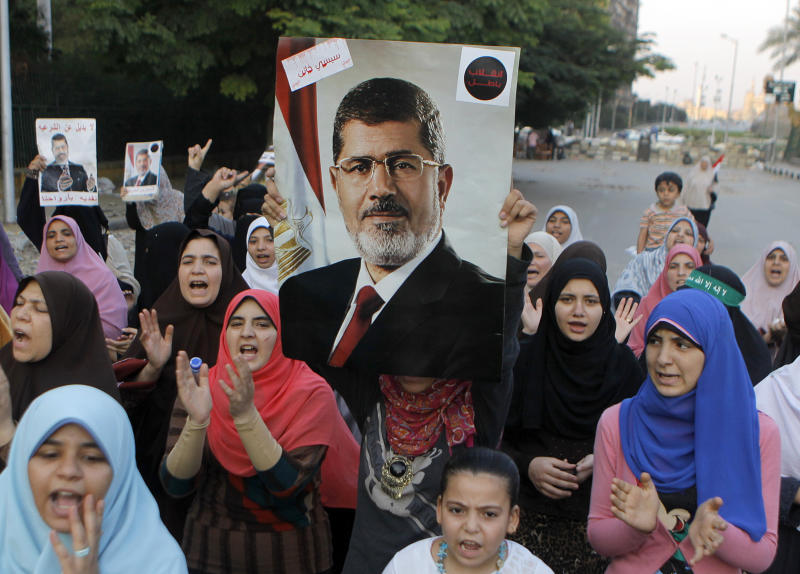 "Supporters of Egypt's ousted President Mohammed Morsi shout slogans as they hold his posters in a park in front of Cairo University, where protesters have installed their camp in Giza, southwest of Cairo, Egypt, Thursday, July 18, 2013. Egypt's military issued a stern warning Thursday against violent protests a day ahead of potentially massive demonstrations called for by supporters of the country's ousted Islamist president. The Muslim Brotherhood, from which ousted President Mohammed Morsi hails, is planning for a massive rally Friday, which they've titled ""Breaking the Coup.""(AP Photo/Amr Nabil)"
