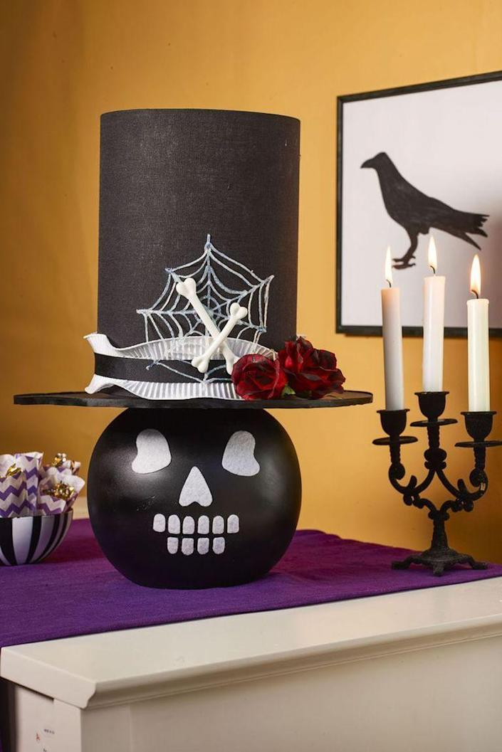 """<p>To make a skull lamp, start by spray painting a round table lamp black and then let dry. Cut facial features from white adhesive felt and press into place. For the top hat, start with a black drum lampshade. Cut a circle of black foam core that's 4 inches wider than shade on all sides for a brim and cover the outer edge with ¼-inch-wide black ribbon. Cut a center hole for the harp, then hot-glue the brim to the bottom of shade and attach it to the lamp. To make the spiderweb, squeeze white dimensional paint onto wax paper in a web shape, and once it's dry, peel it off. Finally, hot-glue the ribbon, spiderweb, faux red roses brushed with black paint, and small bones to the hat.</p><p><a class=""""link rapid-noclick-resp"""" href=""""https://www.amazon.com/Adhesive-Circles-Halloween-Projects-Costume/dp/B08BZF61XN?tag=syn-yahoo-20&ascsubtag=%5Bartid%7C10070.g.2488%5Bsrc%7Cyahoo-us"""" rel=""""nofollow noopener"""" target=""""_blank"""" data-ylk=""""slk:SHOP WHITE ADHESIVE FELT"""">SHOP WHITE ADHESIVE FELT</a></p>"""