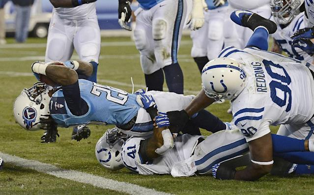 Tennessee Titans running back Chris Johnson (28) gets past Indianapolis Colts defenders Antoine Bethea (41) and Cory Redding (90) as Johnson scores a 7-yard touchdown in the first quarter of an NFL football game Thursday, Nov. 14, 2013, in Nashville, Tenn. (AP Photo/Mark Zaleski)
