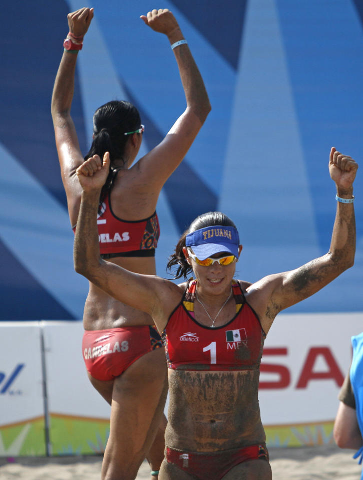 Mexico's Mayra Garcia, front, and teammate Bibiana Candelas celebrate after wining a women's beach volleyball match against Uruguay at the Pan American Games in Puerto Vallarta, Mexico, Tuesday, Oct. 18, 2011. (AP Photo/Ariana Cubillos)