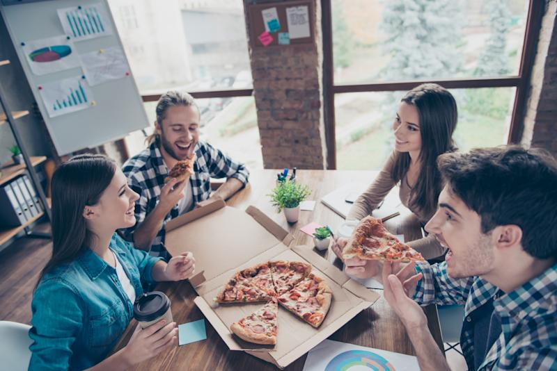 A group of people in an office eating pizza around a desk.