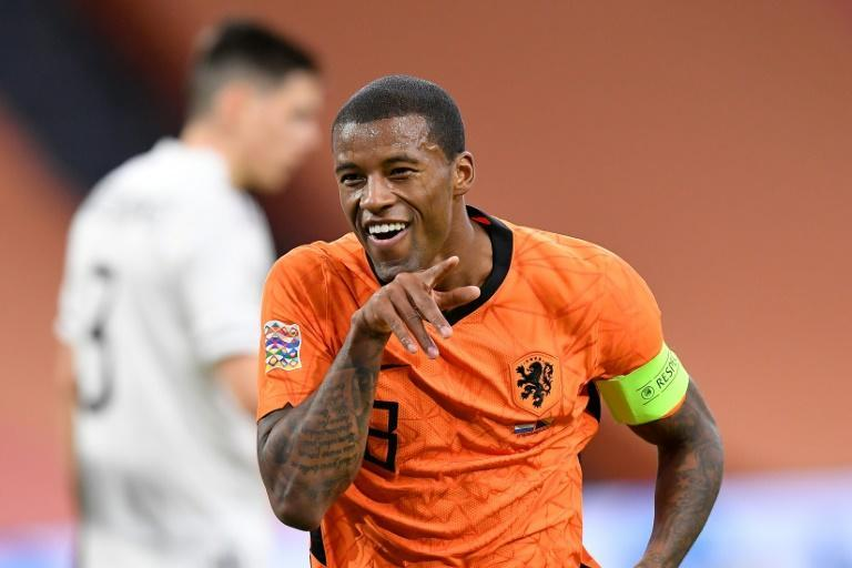 Georginio Wijnaldum's two goals, one celebreated in the style of bsent teammate Virgil van Dijk, put the Netherlands top of Nations League A, Group 1
