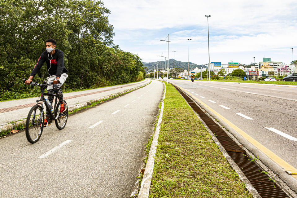 FLORIANOPOLIS, BRAZIL - 2020/07/02: A man wearing a face mask as a preventive measure rides a bicycle along the bike lane at Professor Henrique da Silva Fontes Avenue. (Photo by Ricardo Ribas/SOPA Images/LightRocket via Getty Images)