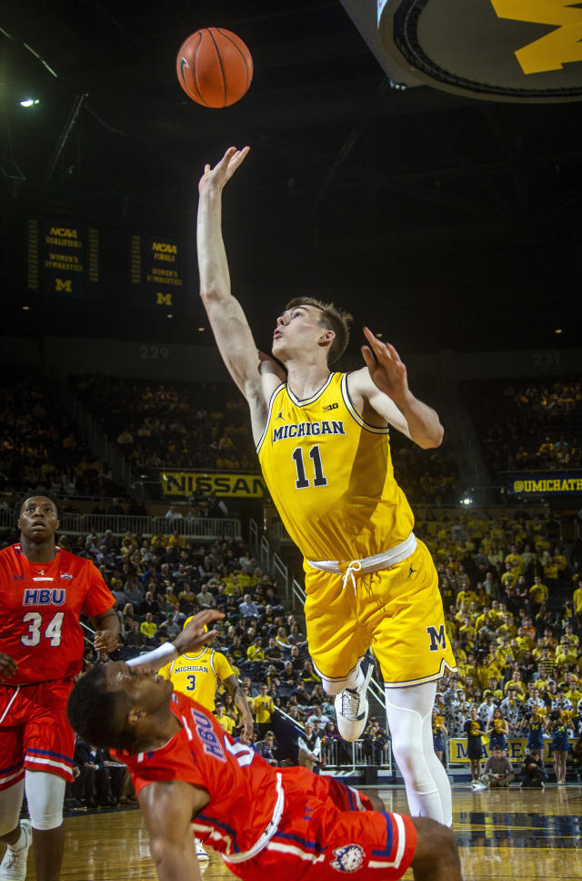 Michigan forward Colin Castleton (11) shoots over falling Houston Baptist guard Ian DuBose during the second half of an NCAA college basketball game in Ann Arbor, Mich., Friday, Nov. 22, 2019. Michigan won 111-68. (AP Photo/Tony Ding)