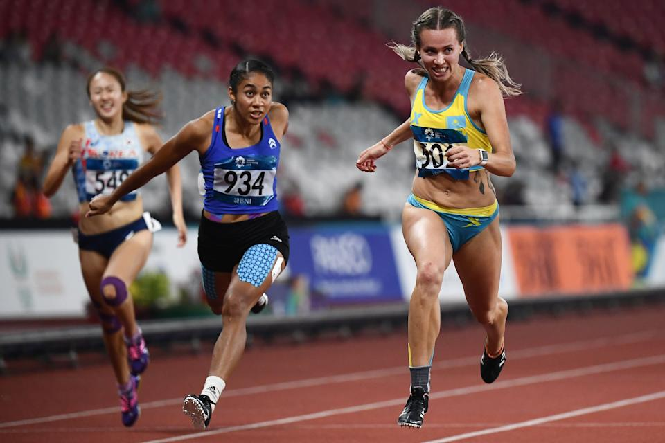 (L-R) Philippines' Kristina Marie Knott and Kazakhstan's Olga Safronova compete in a semi-final heat of the women's 200m athletics event during the 2018 Asian Games in Jakarta on August 28, 2018. (Photo by Jewel SAMAD / AFP)        (Photo credit should read JEWEL SAMAD/AFP via Getty Images)