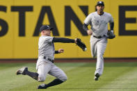 New York Yankees' Brett Gardner, left, tries to catch a ball hit by Cleveland Indians' Cesar Hernandez in the first inning of a baseball game, Thursday, April 22, 2021, in Cleveland. Gardner could not hold onto the ball for the out and Hernandez was safe with a single. (AP Photo/Tony Dejak)