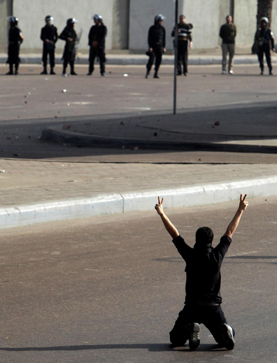 A protester flashes a victory sign in front of police during clashes in Cairo in January 2011REUTERS