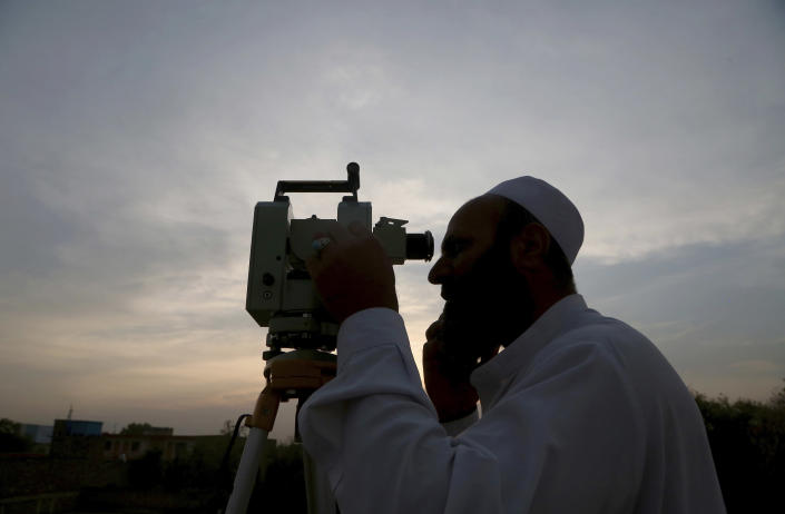A cleric of Pakistan's Moon Sighting Committee searches the sky with a telescope for the new moon that signals the start of the Muslim fasting month of Ramadan, in Peshawar, Pakistan, Tuesday, April 13, 2021. Throughout Ramadan, observant Muslims abstain from any food or drink — including water — from morning to night. (AP Photo/Muhammad Sajjad)
