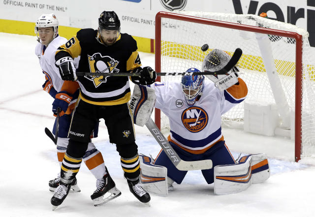 Pittsburgh Penguins' Zach Aston-Reese (46) deflects the puck over the head of New York Islanders goaltender Thomas Greiss (1) and over the goal cage with Anthony Beauvillier (18) defending during the first period of an NHL hockey game in Pittsburgh, Thursday, Dec. 6, 2018. (AP Photo/Gene J. Puskar)