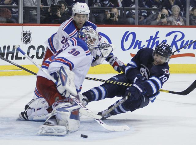 New York Rangers goaltender Henrik Lundqvist (30) saves the shot from Winnipeg Jets' Jim Slater (19) as Rangers' Martin St. Louis looks on defends during second period NHL action in Winnipeg on Friday, March 14, 2014. (AP Photo/The Canadian Press, John Woods)
