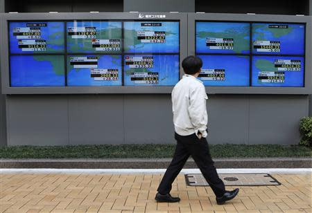 A pedestrian walks past electronic boards showing various countries' share prices outside a brokerage in Tokyo February 6, 2014. REUTERS/Toru Hanai