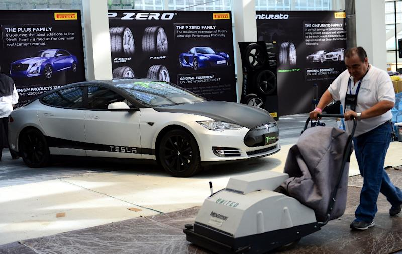 A worker pushes his machine past a 2014 Tesla P85s on display at the LA Auto Show in November 2014 (AFP Photo/Frederic J. Brown)