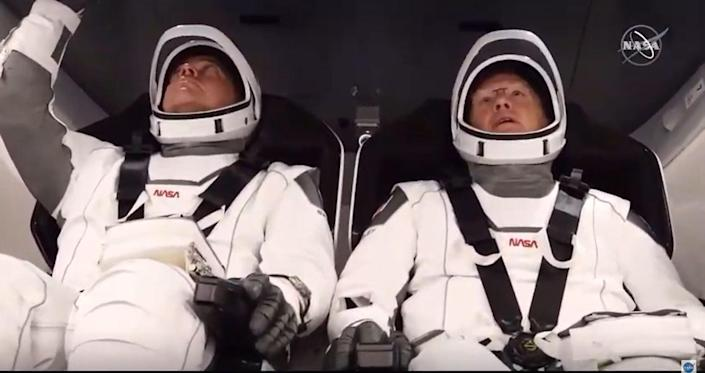 In this still image taken from NASA TV, NASA astronauts Bob Behnken (L) and Doug Hurley are strapped in the SpaceX Crew Dragon capsule at Kennedy Space Center.