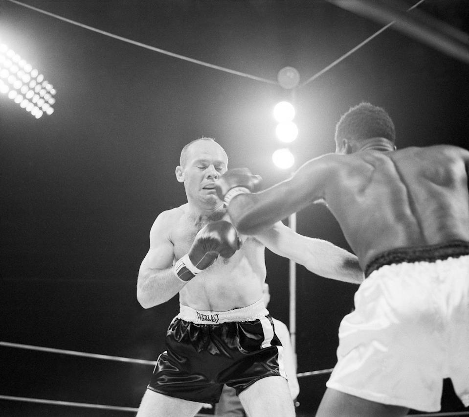 Pete Rademacher closes his eyes and winces as he takes a glancing left hook to the face from Floyd Patterson, the champ, in their heavyweight title boxing match in Seattle on August 23, 1957. Rademacher, in his first pro fight, was knocked down in the third, several times in the fifth, then counted out in the sixth round. (AP Photo)