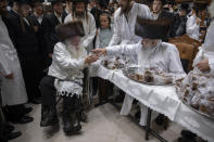 Rabbi Aharon Biderman gives cakes to his followers just before the start of the Jewish holiday of Yom Kippur, in the city of Beit Shemesh, Israel, Wednesday, Sept. 15, 2021. Yom Kippur is Judaism's day of atonement, when devout Jews ask God to forgive them for their transgressions and refrain from eating and drinking, attending intense prayer services in synagogues. (AP Photo/Oded Balilty)