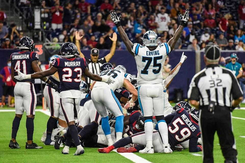 Panthers tackle Cameron Erving, front center, mirrors a referee by holding his arms up to signify a touchdown after quarterback Sam Darnold pushed his way into the end zone during the game at NRG Stadium on Thursday, September 23, 2021 in Houston, TX. The Panthers beat the Texans 24-9, giving them their third win in a row to start the season.