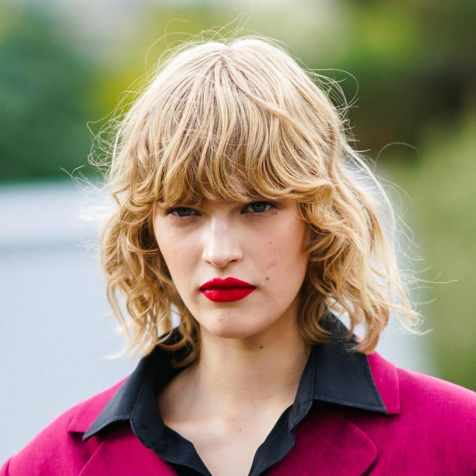 """Another version of this style includes """"lots of messy texture and fringe bangs,"""" according to hairstylist Sally Hershberger — even better if you've got some natural texture, as we see here on this model. Her bangs, which fall just above her eyes, are cut <em>right</em> after the first two bends in her curl pattern, which creates that bouncy, body-full look."""