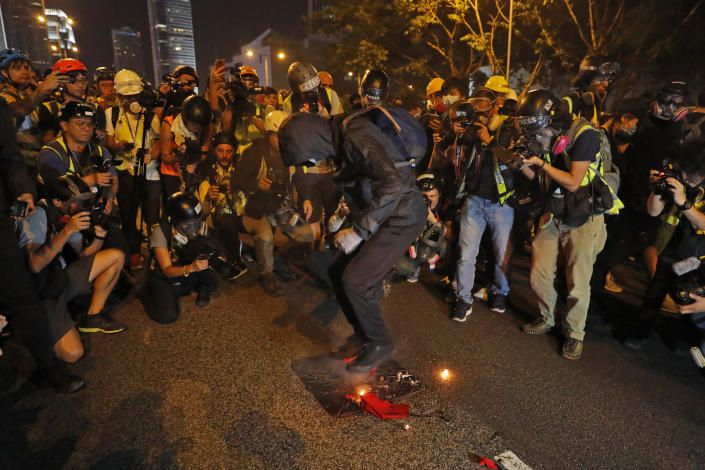 A black-clad protester wearing goggles and a mask stomps on a burning Chinese flag in Hong Kong, Sept. 28, 2019. (Photo: Vincent Thian/AP)