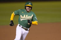 Oakland Athletics' Jed Lowrie rounds third base to score on a single by Matt Chapman during the seventh inning against the Los Angeles Angels in a baseball game Friday, May 28, 2021, in Oakland, Calif. (AP Photo/Tony Avelar)